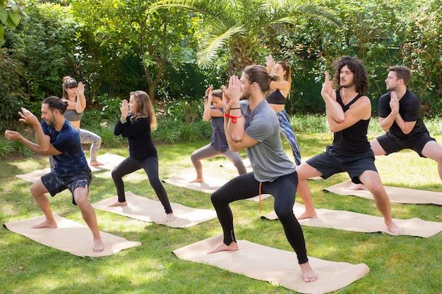 Amantes del yoga disfrutando de la práctica sobre hierba.