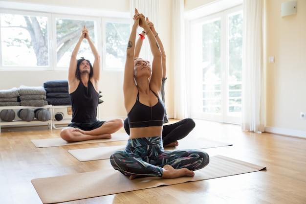 Amantes de yoga pacíficos entrenando en gimnasio