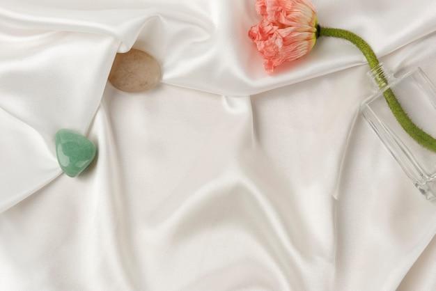 Amapola clavel en un jarrón sobre tela blanca con textura