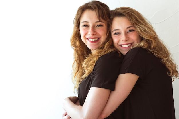 Amar a dos hermanas abrazando contra el telón de fondo blanco