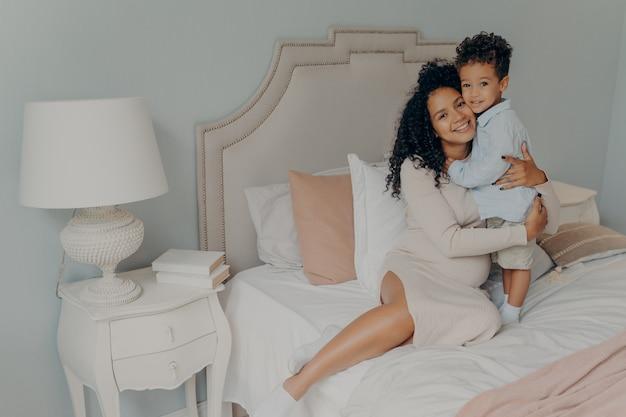 Amar a la madre de la mujer embarazada expresando amor a su pequeño y lindo hijo