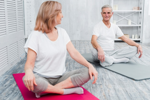 Amar a la pareja feliz mirando el uno al otro antes de comenzar el yoga