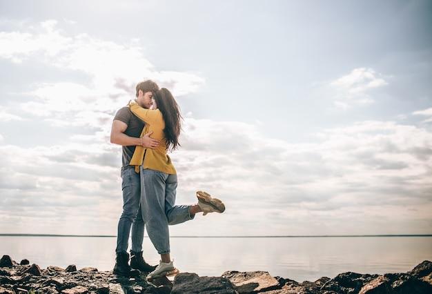 Amar y viajar. una pareja se para contra el telón de fondo de la bahía. un hombre y una mujer están parados cerca de un río o mar sobre piedras y abrazándose.