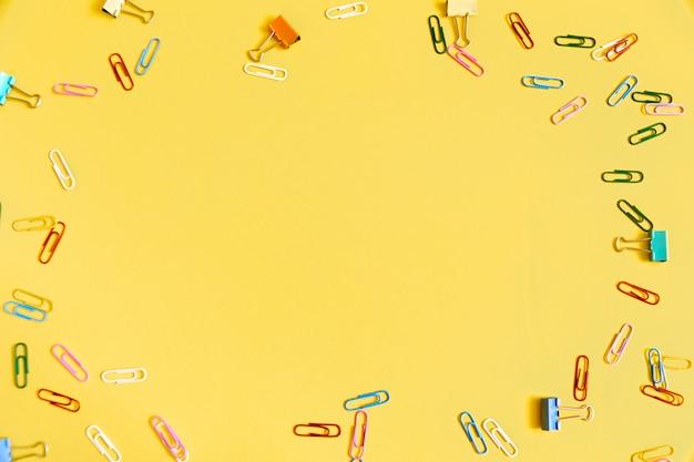Amarillo con clips de colores. marco para texto en el centro.