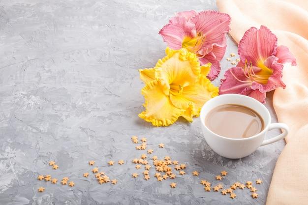 Amarillo y morado lirios diurnos taza de café sobre un fondo de hormigón gris con textil naranja