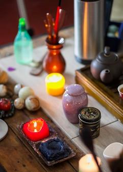 Amarillo; velas encendidas azules y rojas con hervidor de té y canicas bolas de meditación en mesa de madera