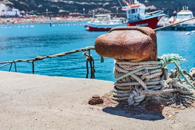 Amarre la cuerda en el puerto, con el mar y los yates