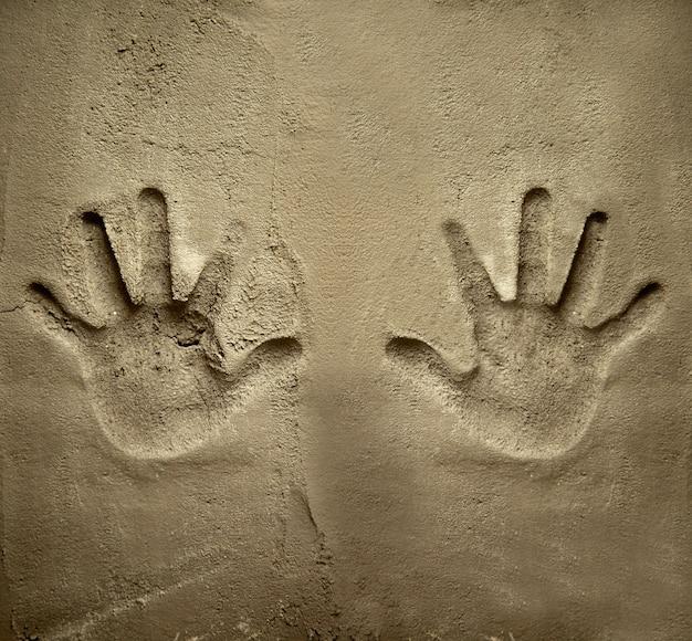 Ambas manos se imprimen en la pared de cemento mortero