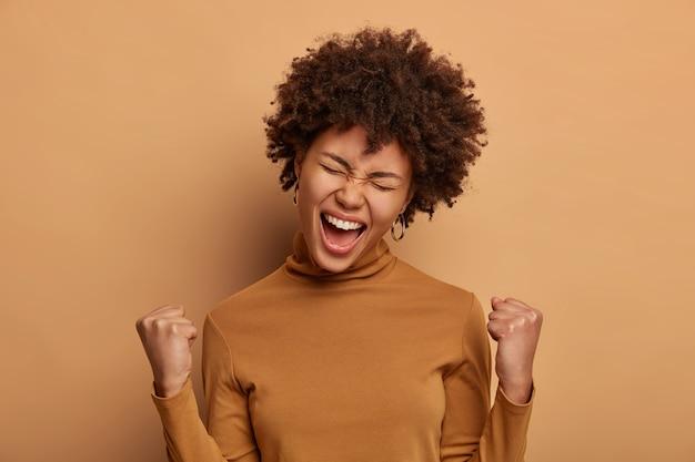 La ambiciosa mujer afortunada y triunfante celebra la increíble victoria con los dos puños cerrados, escucha una excelente noticia y exclama positivamente ¡hurra!