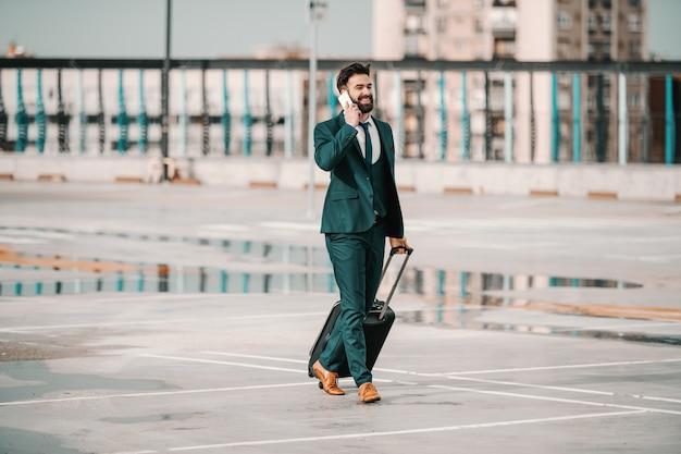 Ambicioso empresario barbudo del cáucaso en traje con teléfono inteligente y equipaje mientras se despierta en el estacionamiento. concepto de viaje de negocios no lo esperes, debes trabajar duro para tenerlo.