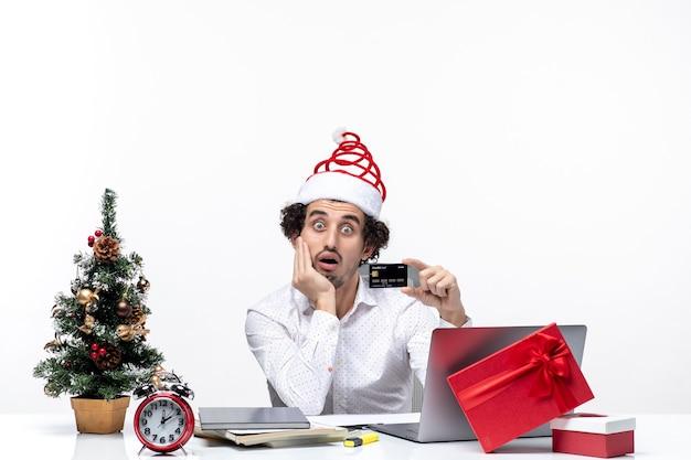 Ambiente festivo de vacaciones con un joven empresario barbudo sorprendido con sombrero de santa claus sosteniendo una tarjeta bancaria y poniendo su mano debajo de la barbilla en la oficina
