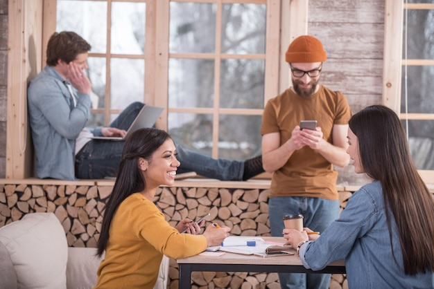 Ambiente informal. jóvenes positivos alegres sentados juntos y hablando entre ellos mientras disfrutan del ambiente