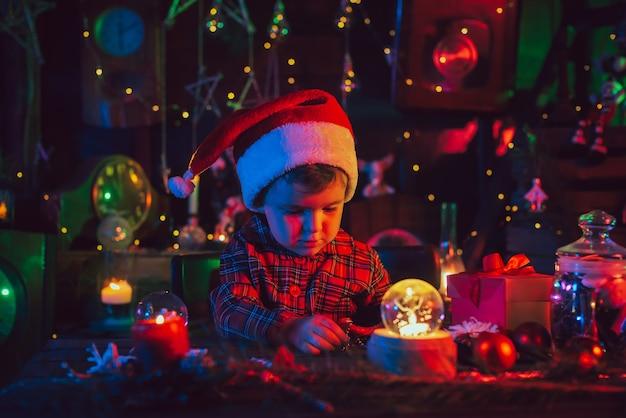 Un ambiente navideño fabuloso y mágico. un niño, el asistente de santa, está sentado en una mesa con adornos navideños. tarjeta postal. luz de color