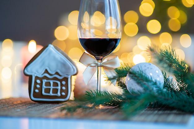 Ambiente navideño festivo con una copa de vino y una casa de pan de jengibre en la mesa de la cocina
