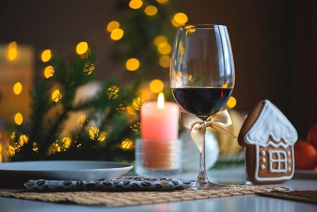 Ambiente navideño festivo con una copa de vino y una vela encendida en la mesa de la cocina