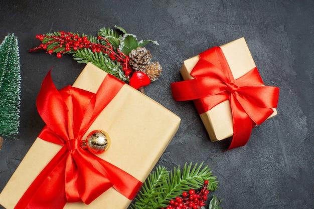 Ambiente navideño con hermosos regalos con cinta en forma de lazo y accesorios de decoración de ramas de abeto sobre un fondo oscuro