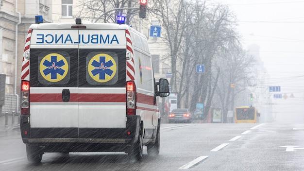 Una ambulancia llevó al paciente a la clínica con los intermitentes encendidos. mal tiempo afuera, lluvia con nieve húmeda.
