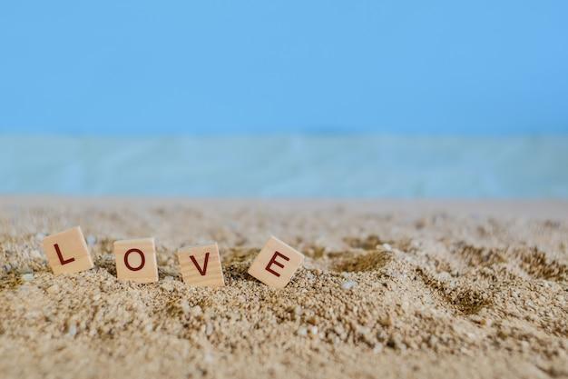 Ame el texto en la madera con la playa tropical de la arena, el concepto del amor y el foco suave.