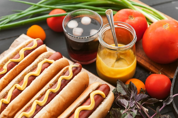 American hot dog con ingredientes sobre un fondo oscuro de madera