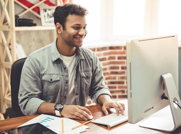 American está sonriendo mientras trabaja con una computadora.