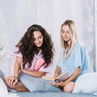 Amiga dos que se sienta en el libro de lectura de la cama