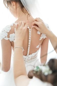 La amiga de la novia prepara a una novia para una boda.