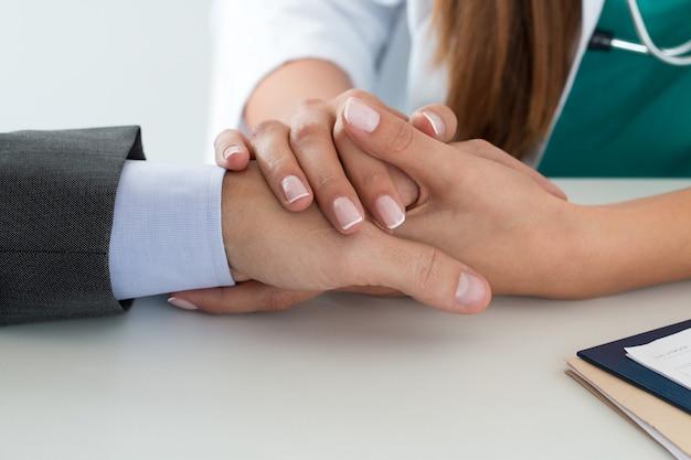Amigable doctora sosteniendo la mano del paciente para apoyarlo