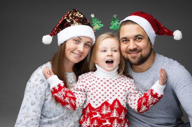 Amigable familia de tres parados juntos y sonriendo