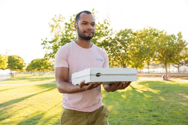 Amigable mensajero positivo del restaurante llevando pizza