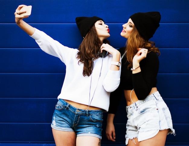 Las amigas adolescentes al aire libre hacen selfie en un teléfono.