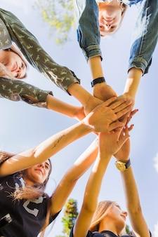Amigas adolescentes apilando las manos juntas