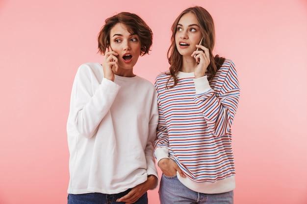 Amigas aisladas sobre pared rosa hablando por teléfonos móviles.