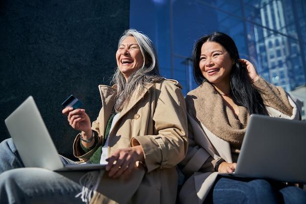 Amigas alegres usando computadoras portátiles para compras en línea