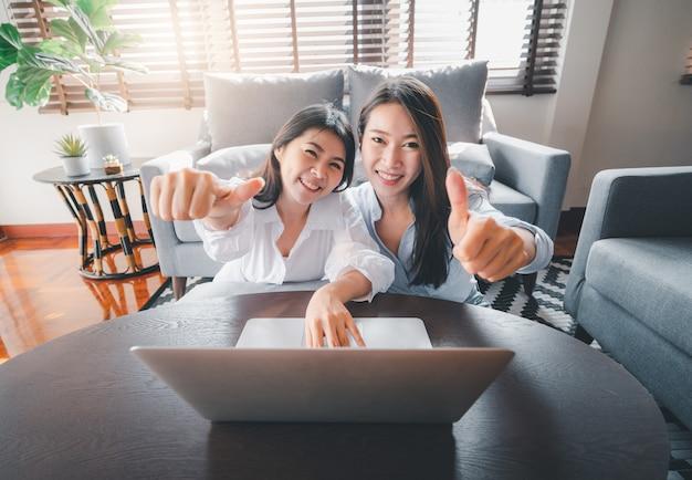 Amigas asiáticas usando laptop haciendo pulgares arriba gesto