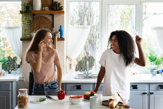 Amigas bailando y divirtiéndose en la cocina