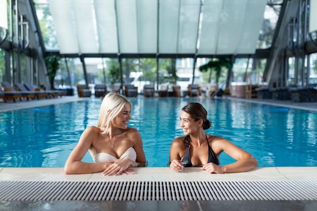 Las amigas beben cócteles mojito en el bar de la piscina usan bikini hotel de lujo cerca de la playa