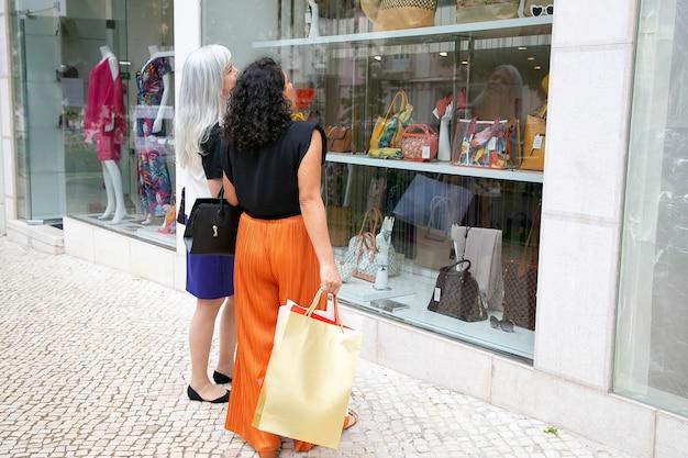 Amigas con bolsas de la compra de pie en la tienda afuera y mirando a la ventana con accesorios. ángulo bajo. concepto de escaparate