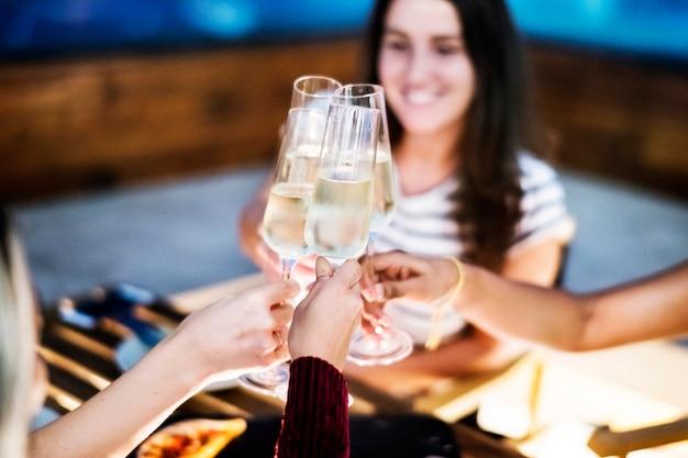 Amigas brindando en la cena juntos en un bar en la azotea