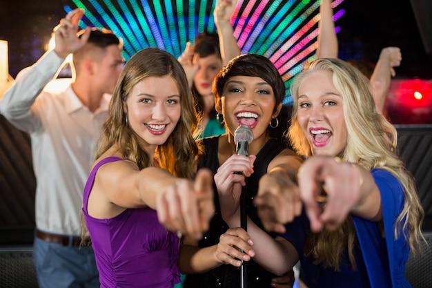 Amigas cantando canciones juntos en el bar