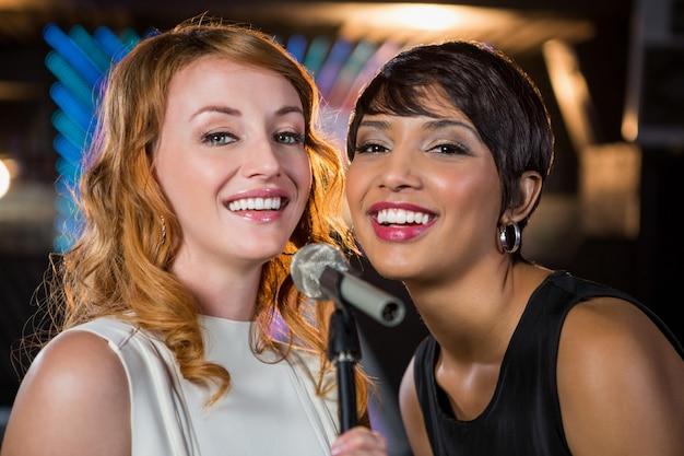 Amigas cantando juntos en el bar