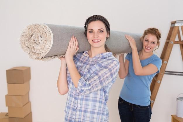 Amigas cargando una alfombra enrollada después de mudarse a una casa