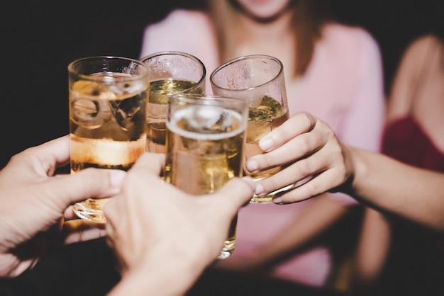 Amigas con cerveza de cristal en una fiesta