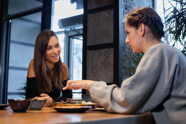 Amigas charlando y tomando unos bocadillos en un café