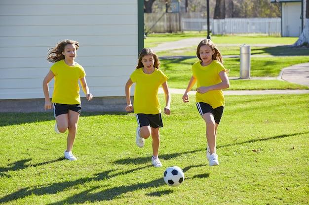 Amigas chicas adolescentes jugando fútbol soccer en un parque