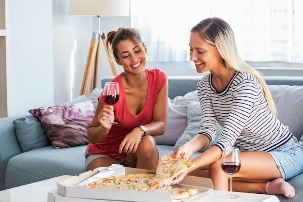 Amigas comiendo pizza con vino en el sofá en casa