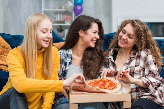 Amigas comiendo pizza