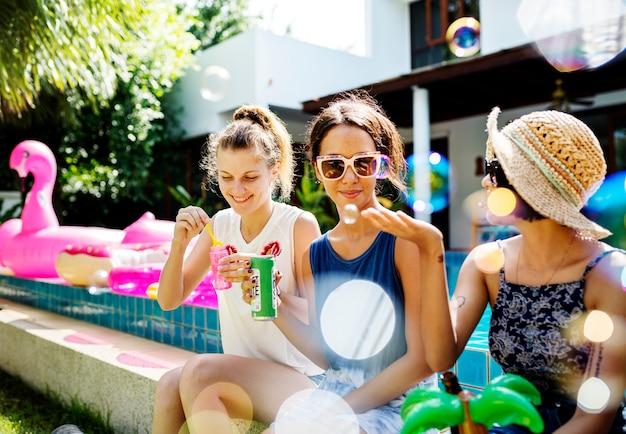 Amigas disfrutando de la hora de verano junto a la piscina y jugando con un burbujeador de jabón