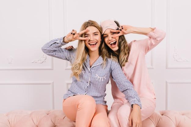 Amigas emocionadas en pijama mostrando signos de paz