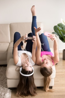 Amigas escuchando música mientras descansan en casa.