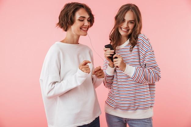 Amigas felices aisladas sobre pared rosa escuchando música con auriculares.